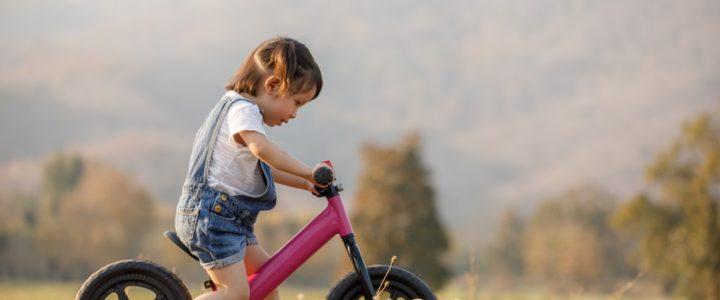 enfant sur une draisienne rose