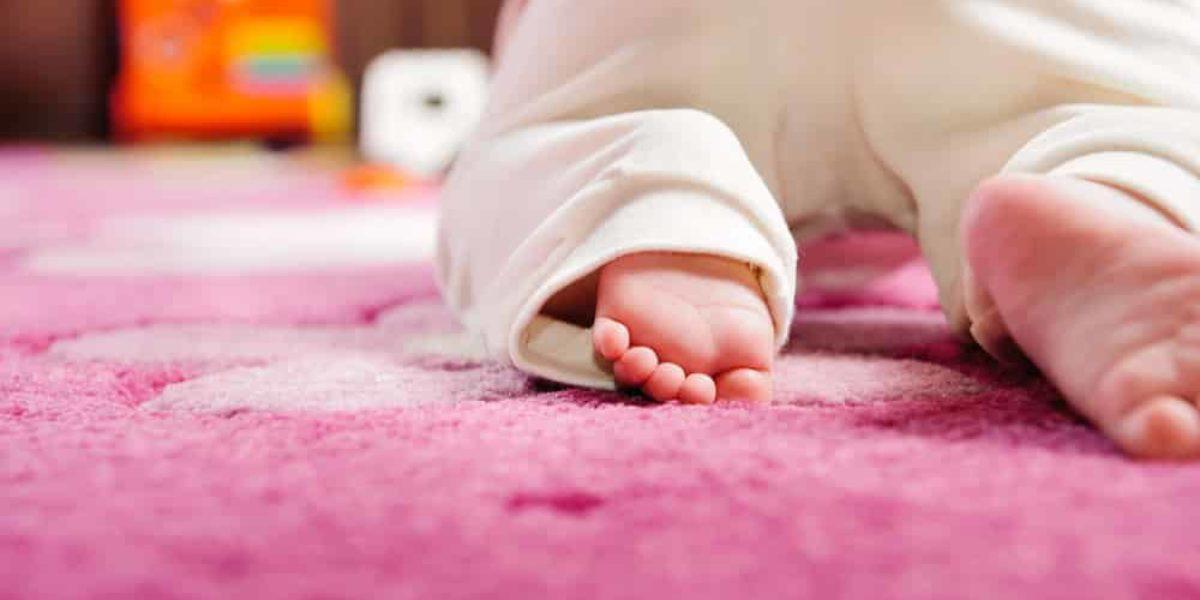 bébé sur un tapis enfant rose