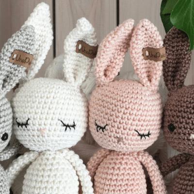 quatre lapins en coton conçus au crochet. Les lapins sont gris, blanc, rose et marron