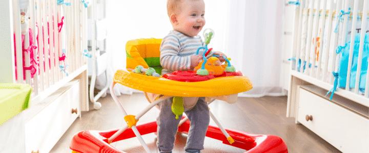 un bébé dans un trotteur rouge et jaune dans sa chambre