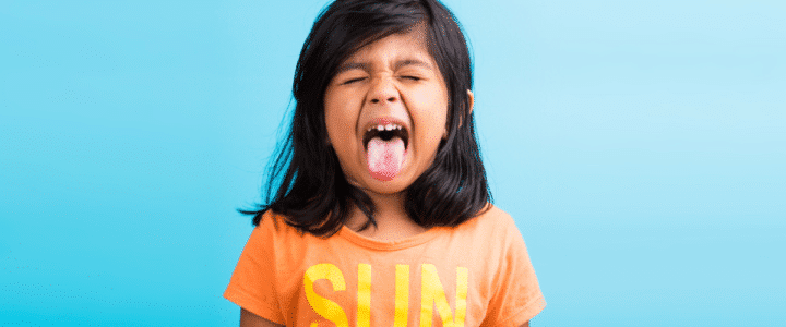 enfant qui tire la langue pour illustrer un article sur les enfants hyperactifs