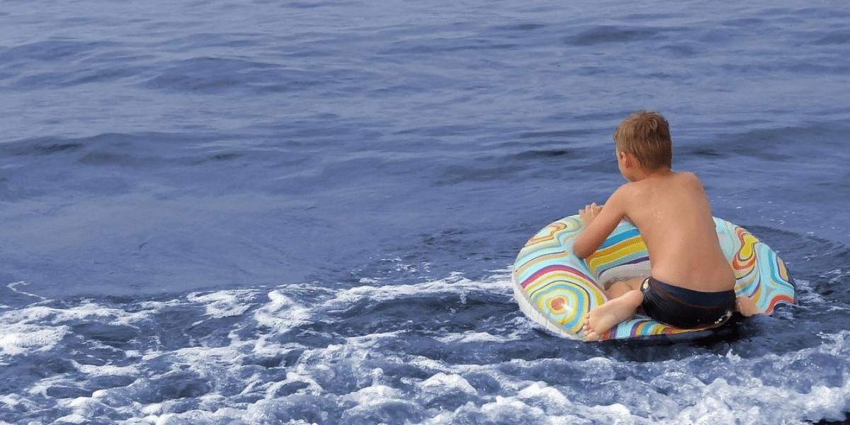 garçon avec bouée et maillot de bain dans la mer