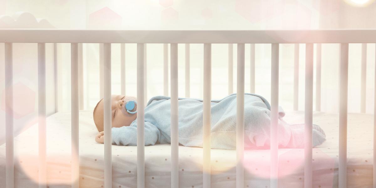 un bébé dort dans son petit lit à barreau sur son matelas bio