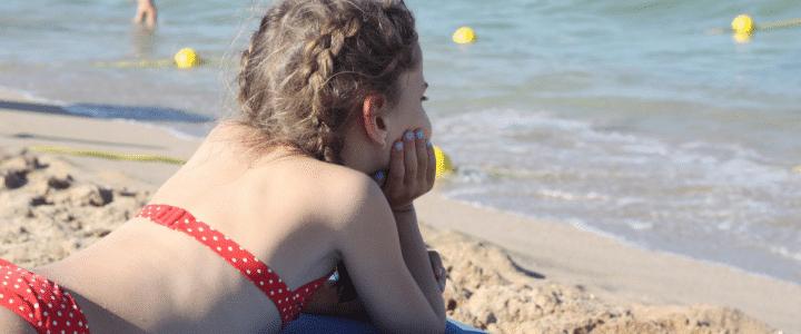 petite fille sur la plage en maillot de bain rouge